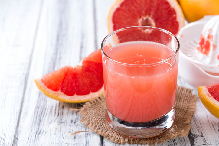 Pure Grapefruit Juice (close-up shot) on rustic wooden background
