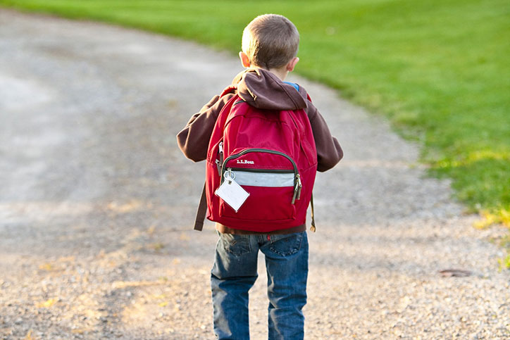 Young child walks down gravel path with red backpack.