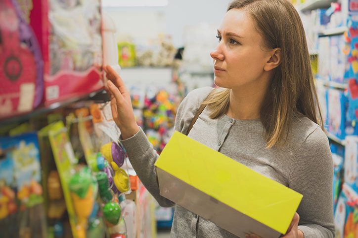 Women perusing toy shelf at store with one toy already in hand.