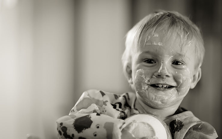 Black and white photo of a small toddler with lotion spread across his face.