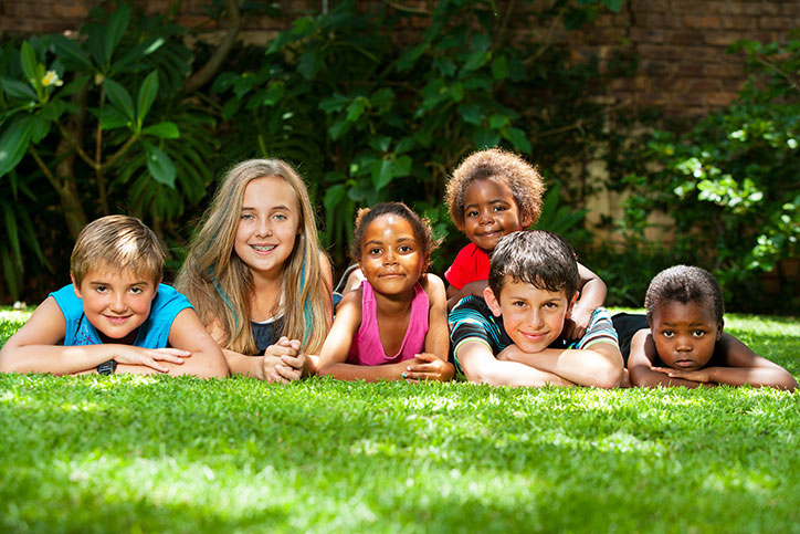 Diverse group of children laying on the grass, facing the camera.