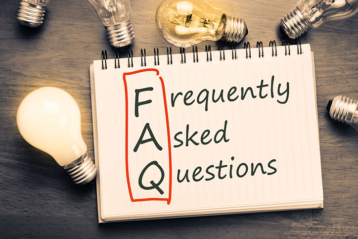 Open spiral-bound notebook on a table surrounded by lightbulbs with the FAQ in Frequently Asked Questions circled in red.