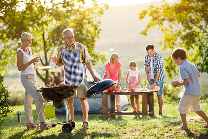 Happy family camping and cooking barbecue outside