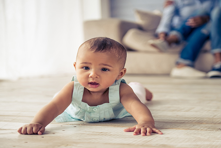 Afro-American baby girl is looking forward with interest while crawling on wooden floor at home