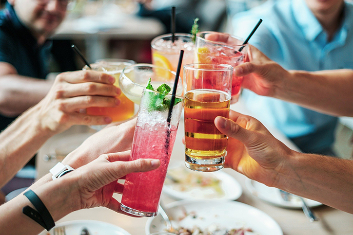 A group of hands holding alcoholic drinks for a cheers