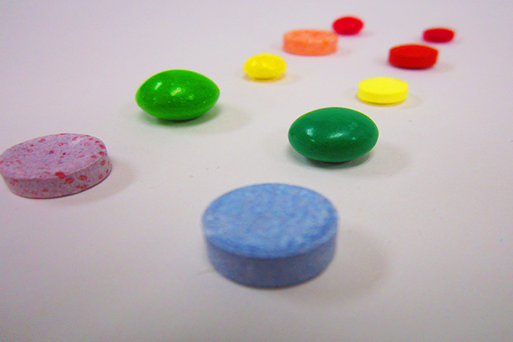 Two rows of colorful circular items, one row is candy and the other row is medicine