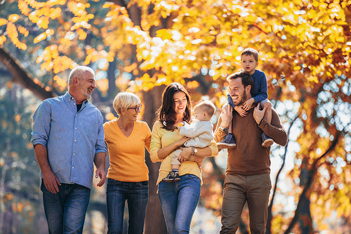 Multi-generation family walking in autumn park