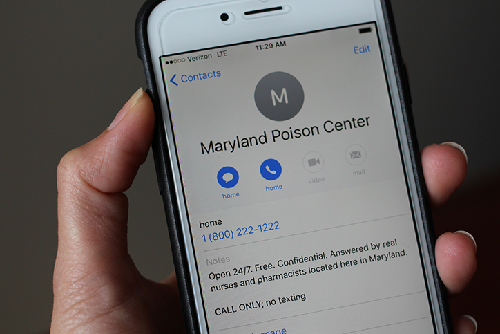 Hand holding a cell phone with the screen on a contact for Maryland Poison Center with the phone number 1-800-222-1222