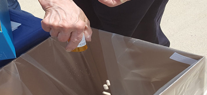 Hand holding a medicine bottle with pills falling into a collection box.