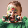 Humorous photo of cute cheerful child girl showing her hands and face painted in bright colors.