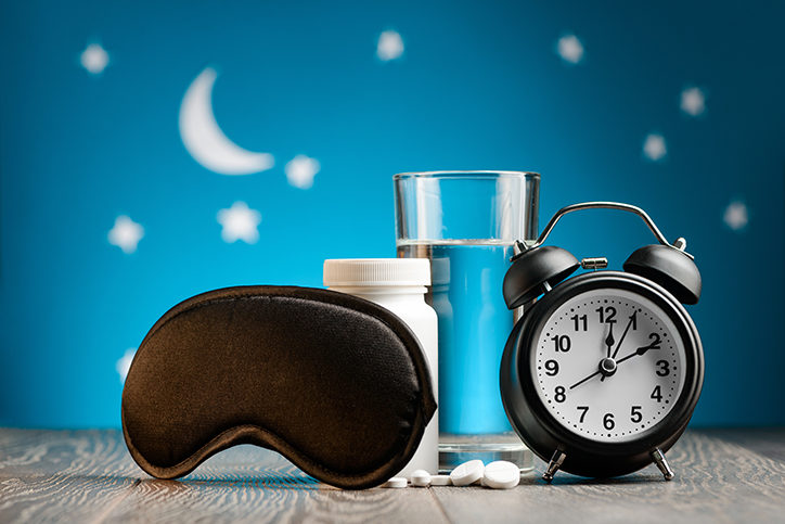 Eye mask, pills and alarm clock on a bedside table over night sky. Getting rid of insomnia, remedies for good restful sleep.