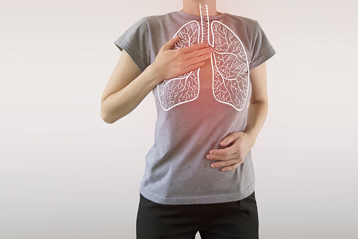 person in a gray shirt holding their chest and stomach with their hands. There is a white outline of the lungs with a red glow behind it.